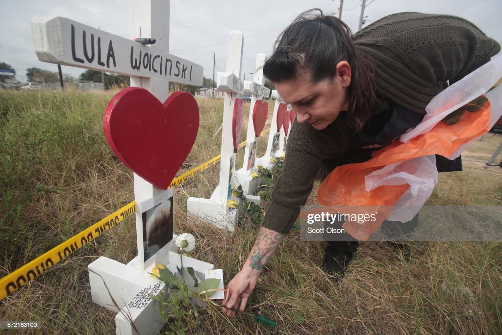 Joyce Mires leaves flowers at a memorial where 26 crosses were placed to honor the 26 victims killed at the First Baptist Church of Sutherland Springs on November 9, 2017 in Sutherland Springs, Texas. On November 5, a gunman, Devin Patrick Kelley, shot and killed the 26 people and wounded 20 others when he opened fire during Sunday service at the church.