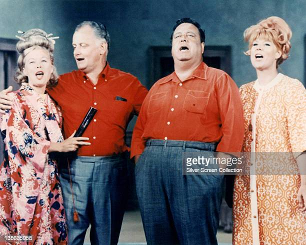 Joyce Randolph US actress Art Carney US actor Jackie Gleason US actor and Audrey Meadows US actress stand in a group singing in an image issued...