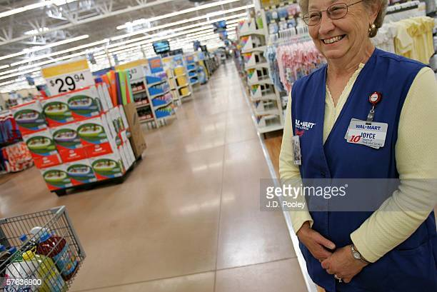 Joyce Smith who has been working at WalMart for the past 13 years smiles at a customer during the grand opening of a new 2000 square foot WalMart...