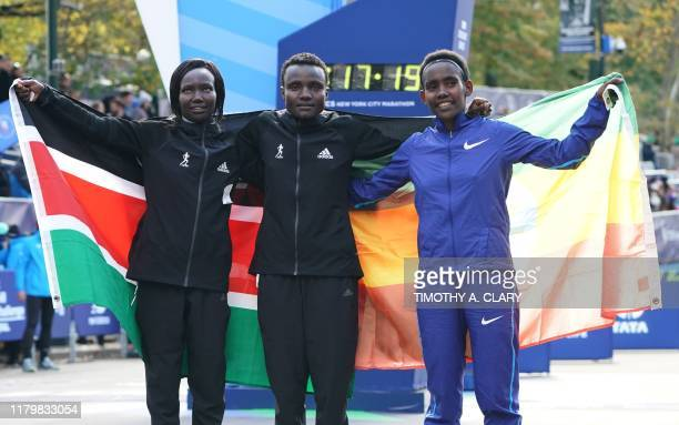 Joyciline Jepkosgei of Kenya poses with second place winner Mary Keitany of Kenya and third place Ruti Aga of Ethiopia after the Professional Women's...