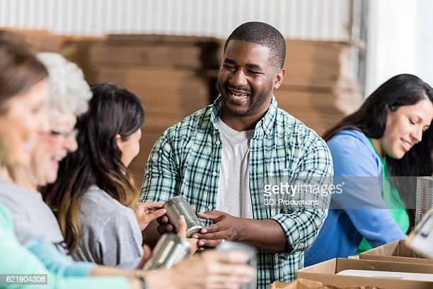 Joyful African American man accepts donation at food bank