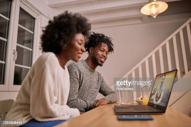 joyful black couple watching a clip on their laptop - mindzoom 2 stock pictures, royalty-free photos & images
