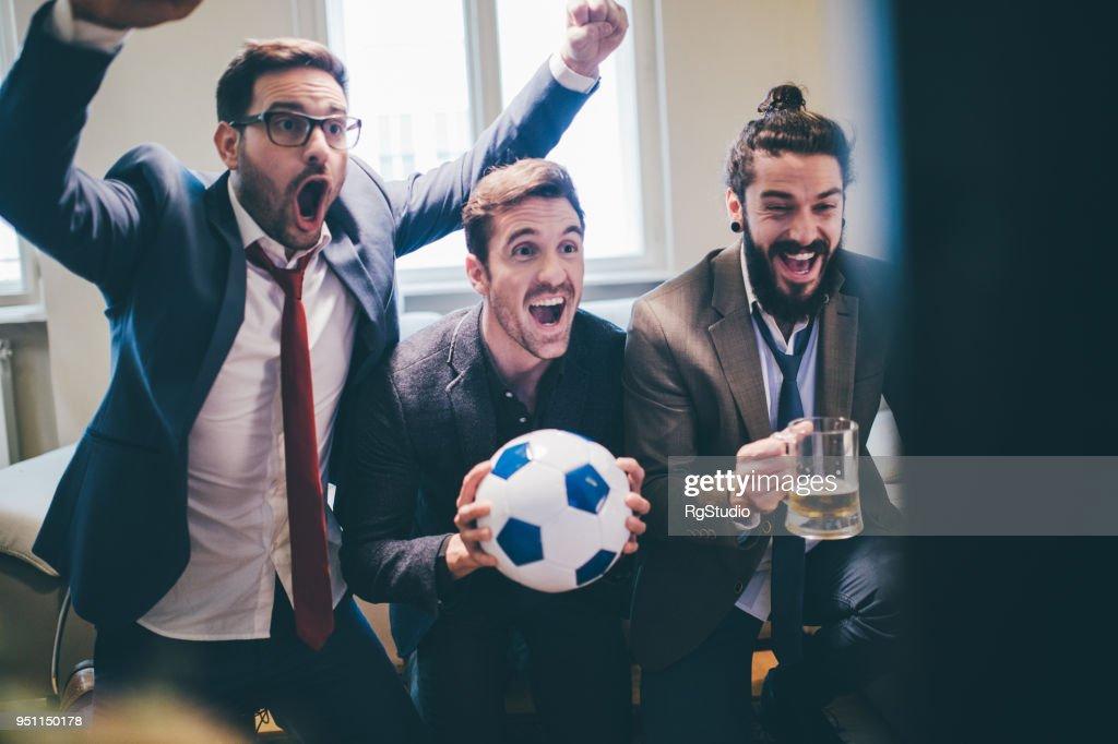 Freudige Geschäftsleute unterstützen ihre Lieblings-Fußball-Teams in Aufregung : Stock-Foto