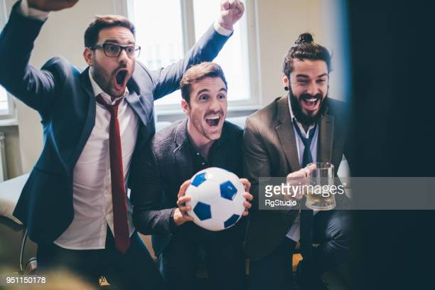 joyful business men supporting their favorite football teams in excitement - mens world championship stock photos and pictures