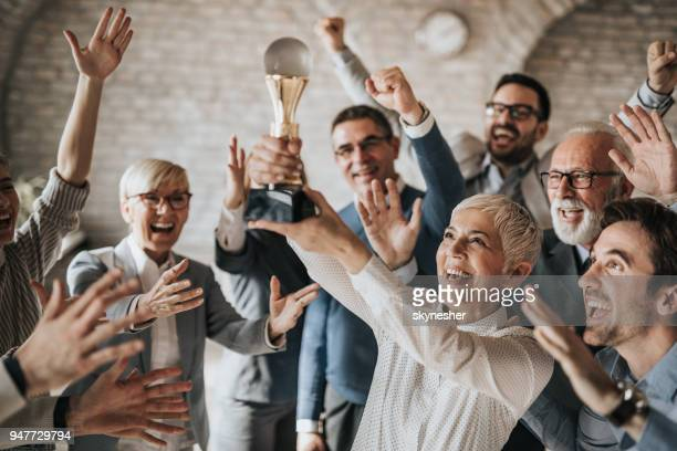 joyful business team celebrating their achievement with a trophy in the office. - award stock pictures, royalty-free photos & images