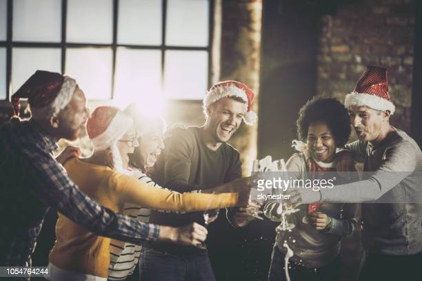 joyful business team having fun while opening champagne during christmas celebration in the office. - work party stock pictures, royalty-free photos & images