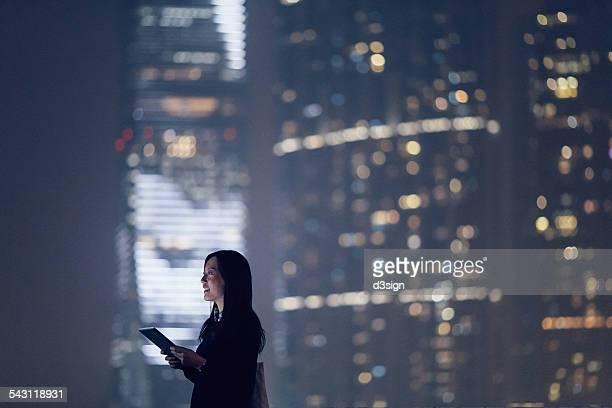 Joyful businesswoman using digital tablet in city