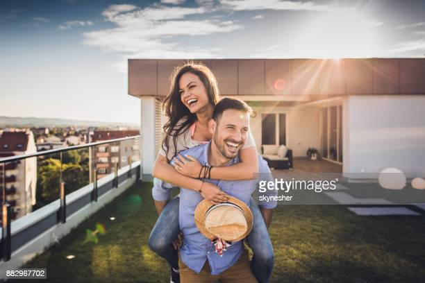 joyful couple having fun while piggybacking on a penthouse terrace. - springtime stock pictures, royalty-free photos & images