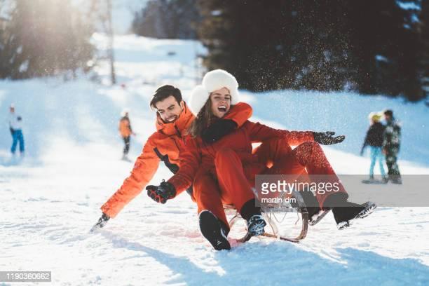 fröhliches paar rodeln im winterurlaub - schlitten stock-fotos und bilder