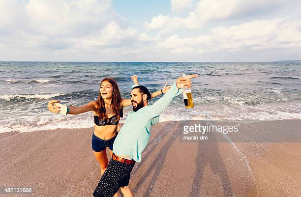 Joyful couple taking a selfie at the beach