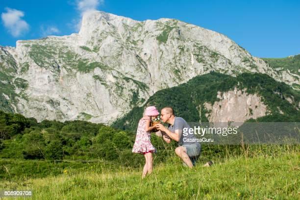hija alegre y padre picking up hierbas y flores silvestres en el prado de la montaña - dan peak fotografías e imágenes de stock