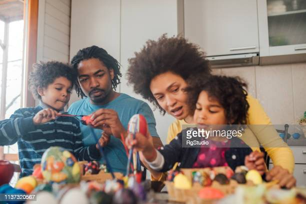joyful family decorating easter eggs - african american easter stock photos and pictures