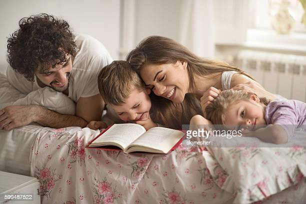 Joyful family reading a book and laughing in the bedroom.