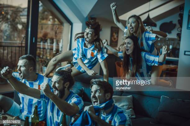 Joyful fans screaming while celebrating the victory on their soccer team in the living room.