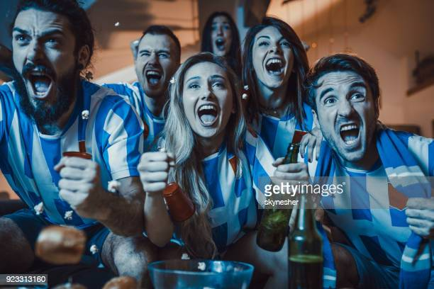 Joyful fans screaming while watching soccer match on TV at home.