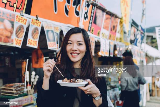 joyful female tourist enjoying japanese style snacks from local street vendor while travelling in japan - market stall stock pictures, royalty-free photos & images