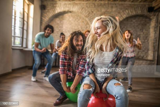 joyful freelance workers having fun in space hopper challenge at casual office. - hoppity horse stock photos and pictures