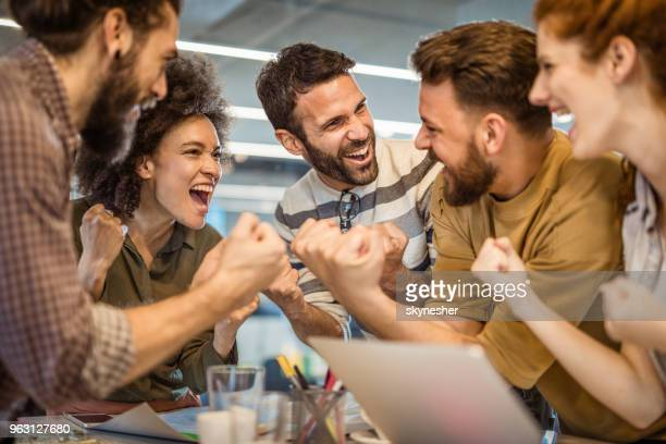 joyful freelancers screaming while celebrating their business success in the office. - punching the air stock pictures, royalty-free photos & images