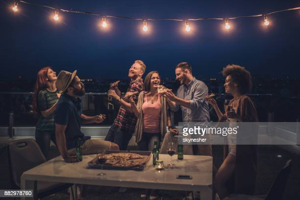 joyful friends having a dinner party during the night on a terrace. - friends stock pictures, royalty-free photos & images