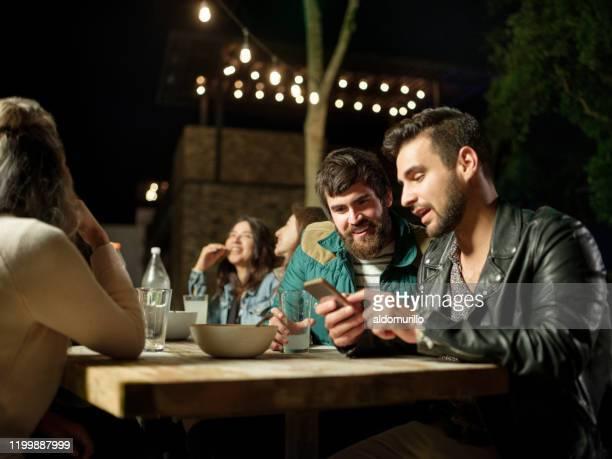 joyful friends having a dinner party during the night - carne assada imagens e fotografias de stock