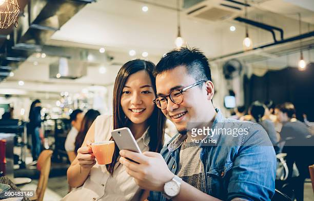 joyful friends laughing at a smartphone in a cafe - asian drink stock photos and pictures