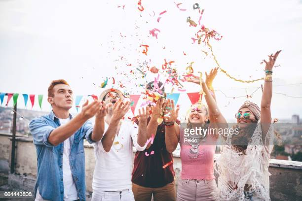 Joyful friends with confetti at the rooftop party
