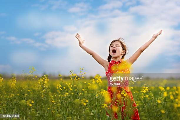 Joyful girl in blooming field