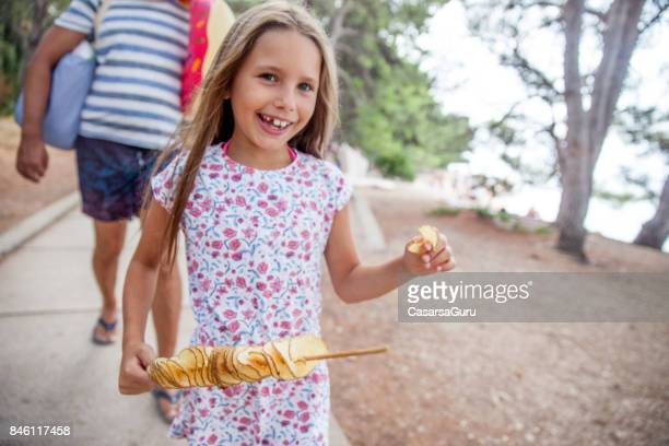 Joyful Girl On A Coastline Walkway Having Snack Of Potato Slices On Stick