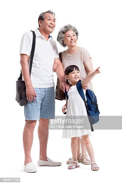 Joyful grandparents and granddaughter looking at view