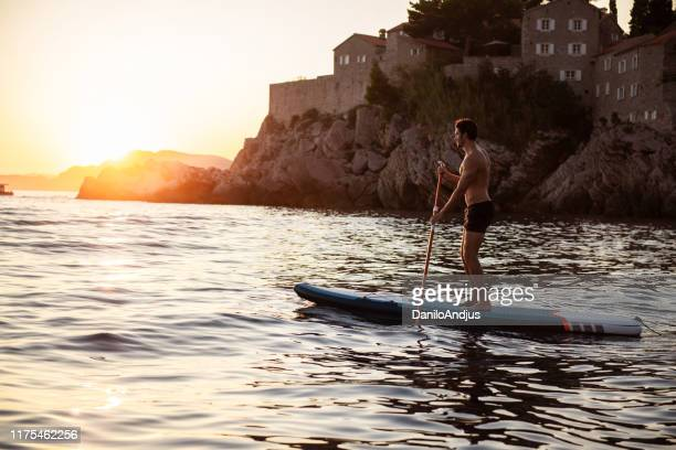 joyful guy paddling at the sea - water sport stock pictures, royalty-free photos & images