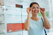 Joyful happy woman trying some eyeglasses on