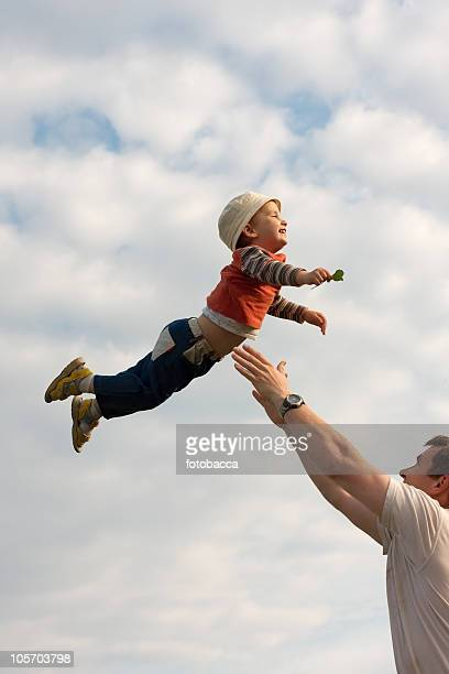 Joyful image of a father playfully throwing son in the air