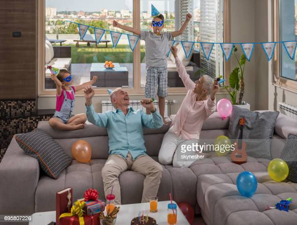 joyful kids and their grandparents having fun on a birthday party in a penthouse. - penthouse girls stock pictures, royalty-free photos & images