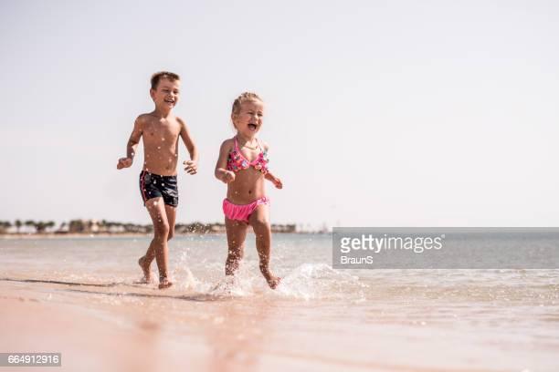 glada barn ha roligt medan du kör på stranden. - förföljande bildbanksfoton och bilder