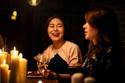 Joyful Korean woman in her 30s laughing with friend over dinner - gettyimageskorea