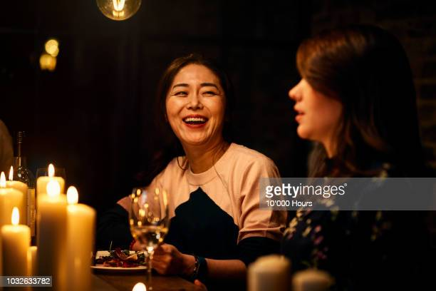 joyful korean woman in her 30s laughing with friend over dinner - candlelight stock pictures, royalty-free photos & images