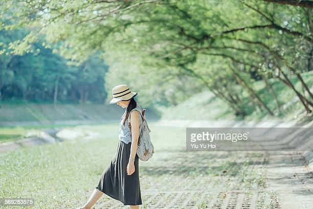 Joyful lady playing with leaves in park relaxingly