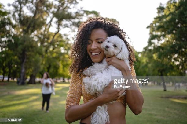 joyful latin american woman hugging her dog - lap dog stock pictures, royalty-free photos & images