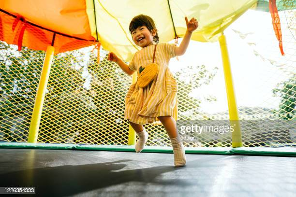 joyful little asian toddler girl smiling happily and having fun jumping in a bouncy castle in a outdoor playground - preschool child stock pictures, royalty-free photos & images