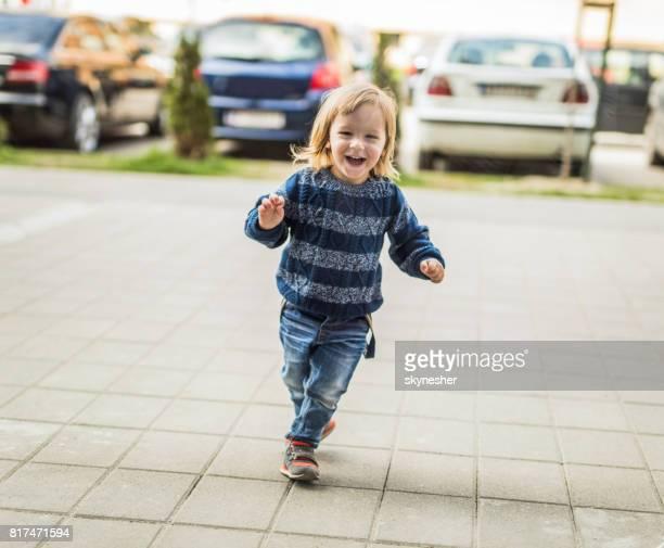 うれしそうな少年が歩道上で実行しながら楽しい時を過します。