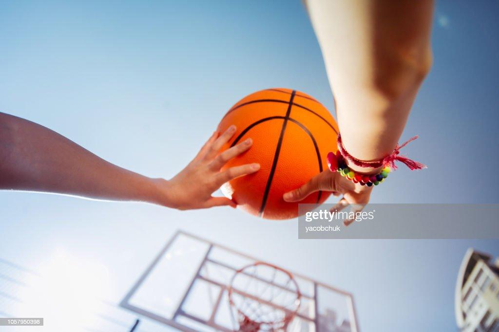 Joyful little female preparing to throw the ball : Stock Photo