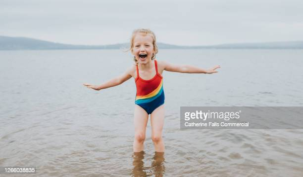joyful little girl paddling in the sea, wearing a rainbow swimming costume - coastline stock pictures, royalty-free photos & images
