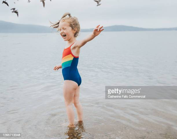 joyful little girl paddling in the sea, wearing a swimming costume while seagulls fly overhead - beach stock pictures, royalty-free photos & images