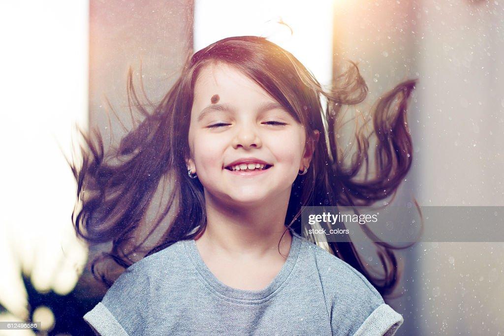 joyful little girl with flying hair : Foto stock