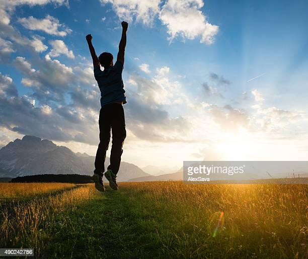 Joyful man jumping on a meadow at sunset