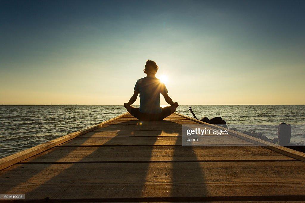 Joyful man meditating on pontoon over a lake at sunrise : Stockfoto