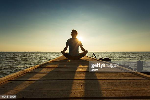 joyful man meditating on pontoon over a lake at sunrise - meditieren stock-fotos und bilder