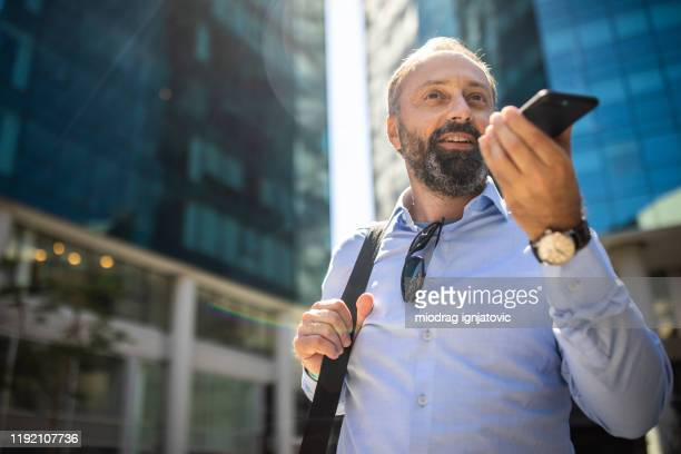 joyful mature man using cellphone on the street - speech recognition stock pictures, royalty-free photos & images