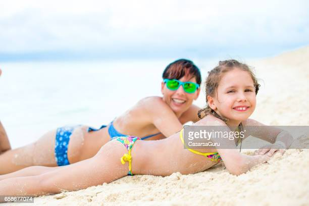 joyful mother and daughter enjoy lying on the sandy tropical beach - little girl laying on the beach stock photos and pictures