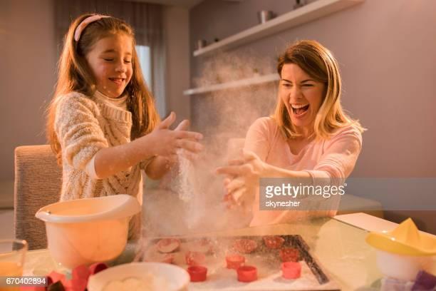 Vrolijke moeder en dochter plezier met bloem terwijl het maken van cookies.